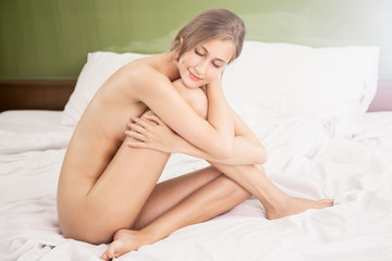 portrait of healthy smiling naked woman with closed eyes on the