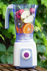 Electric blender with fruits in it