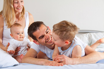 Glückliche Familie kuschelt im Bett