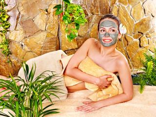 Girl having clay facial mask.