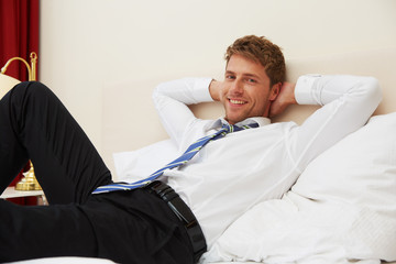 Mann auf Hotelbett
