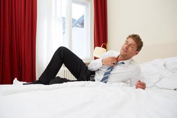 Mann entspannt auf Hotelbett