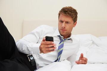 junger Mann schaut auf Smartphone