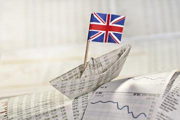 Papierschiff mit britischer Flagge auf Börsennachrichten