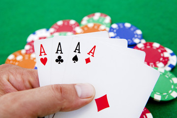 poker, four aces holded in hand over a casino table full with ch