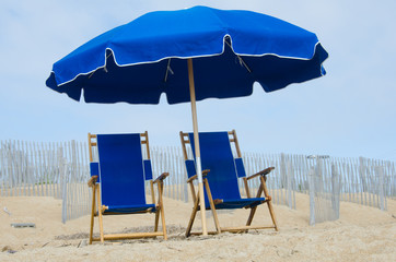 Blue beach umbrella and two matching chairs at the seashore
