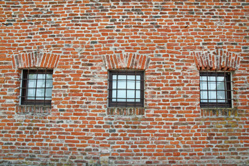 brick wall with iron lattice window of an ancient prison