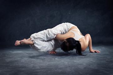 frau in yoga pose mit weißer hose