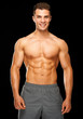 Portrait of muscular sporty man standing on black