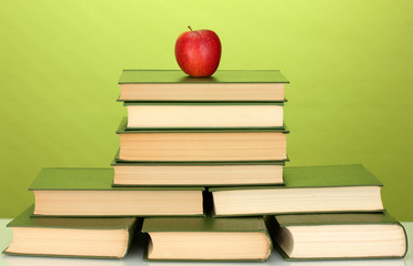 pile of books with apple on green background close-up