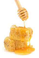 golden honeycombs and wooden drizzler with honey isolated