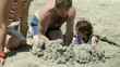 Happy family playing in sand on the beach
