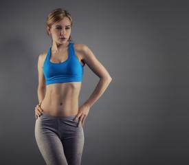 junge frau in fitness dress vor grauem hintergrund