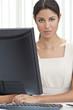 Hispanic Latina Woman or Businesswoman in Office Using Computer