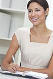 Hispanic Latina Woman or Businesswoman in Office Writing