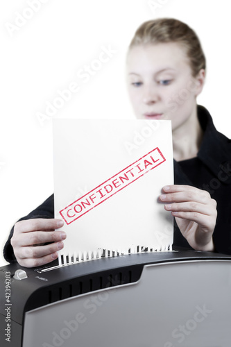 woman shredding a confidential paper