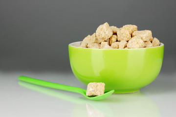 Colorful bowl with brown cane sugar cubes with colorful spoon