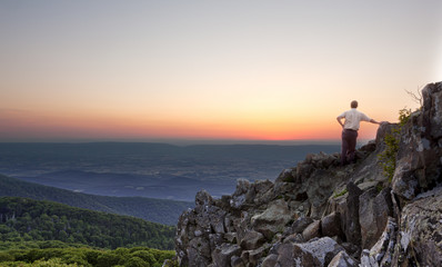 Senior man watches sunrise over blue ridge