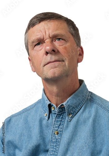 Senior man in blue shirt looks pensive