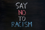 Say no to racism written on a smudged blackboard background poster
