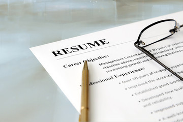 Closeup of resume with pen and glasses on the table