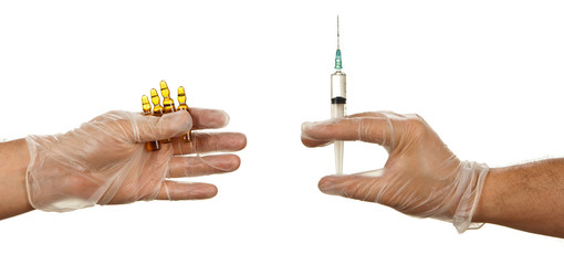 Hand holding ampules with yellow drug and hand in latex glove ho