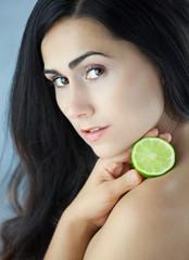 Piękna dziewczyna  trzymająca przekrojoną kwaśna limonkę