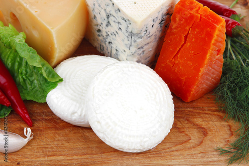 delicatessen types of cheese on wooden board