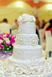 white floral wedding cake on restaurant interior background