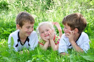 Zwei Jungen und ein Mädchen auf einer Wiese