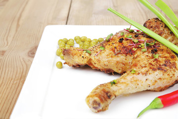 chicken garnished with green sweet peas and red hot pepper