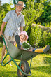 Grandfather giving granddaughter ride in wheelbarrow