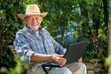 Senior using a laptop in the garten