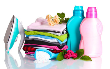 Detergent with washing powder and pile of colorful clothes
