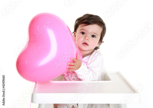 Baby holding heart shaped balloon