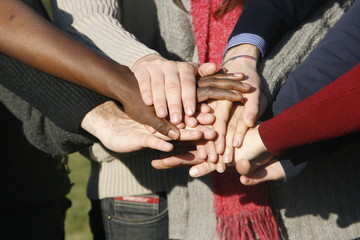 Young group with hands stacked together