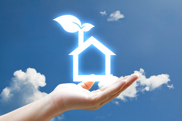 Hand and vivid eco houes icon on sky