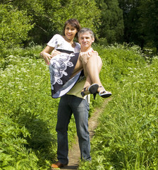Man with woman on hands on summer meadow