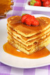 Stack of heart shaped pancakes with syrup and strawberry