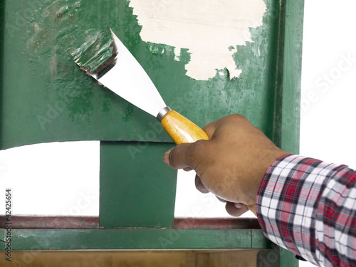 man peeling paint on the chair