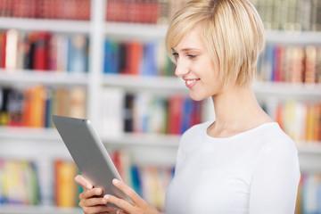 junge frau mit tablet-pc in der bibliothek