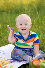 baby boy with Down syndrome painting finger paints