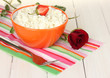 cottage cheese with strawberry in orange bowl, fork and flower