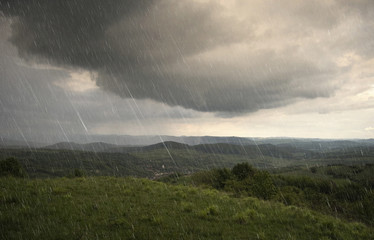 landscape with rain and dramatic clouds over hills