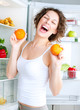 Dieting concept. Laughing Young Woman Eats Fresh Fruit