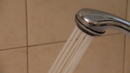 Closeup of a shower head with sprinkling water.