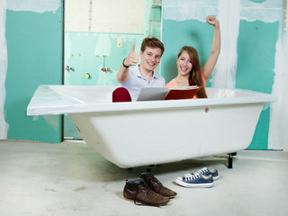 Young couple celebrate her new bathtub in a building lot