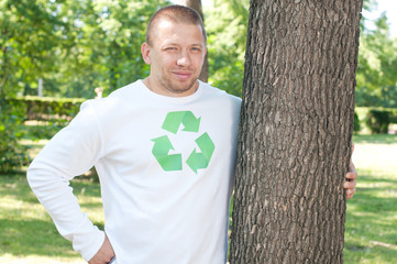 Man with recycle logo on his shirt embracing tree in a park