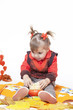 little girl in an orange vest plays with big pumpkins