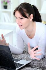 Upset woman looking in laptop